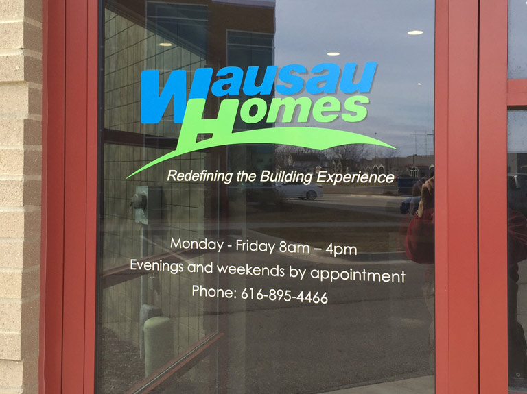 Green, blue and white vinyl lettering on glass for Wausau Homes.