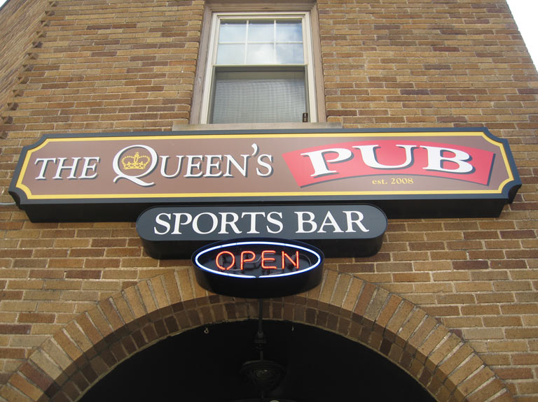The Queen's Pub bar signs on a brick wall