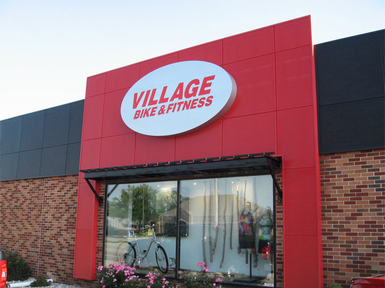 Village Bike and Fitness oval shaped sign mounted on front of building