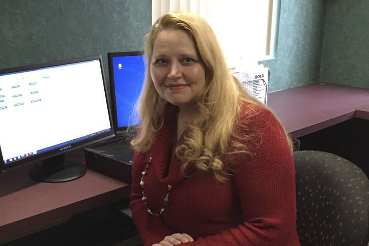 Amy Simonte sitting at her desk in front of computer