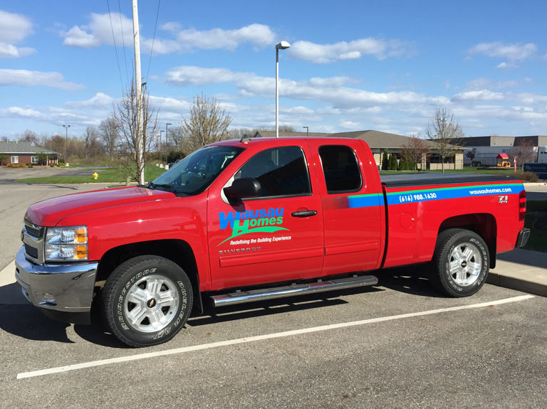 Red truck with vinyl lettering on the sides for Wausau Homes