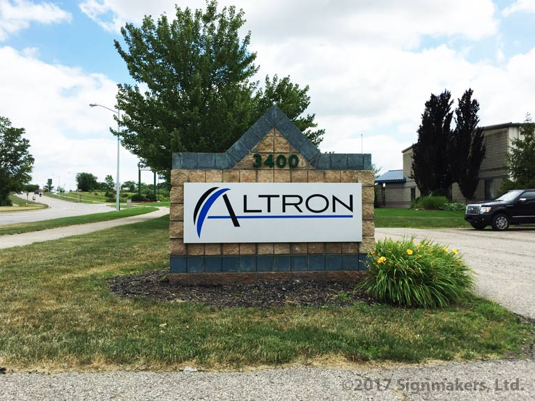 A silver sign panel mounted to a small brick wall with the word Altron in black and blue.