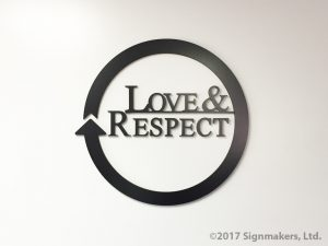 Black plastic letters on a white wall, in a circle pattern, reading Love and Respect.